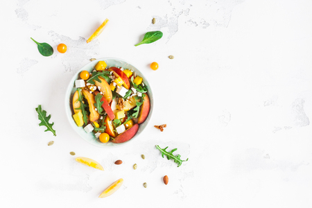 Peach salad. Spinach leaves, arugula, sliced peaches, mango, nuts, feta cheese on white background. Healthy food concept. Fat lay, top view