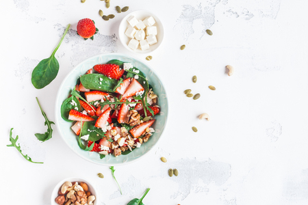 Strawberry salad. Spinach leaves, sliced strawberries, nuts, feta cheese on white background. Healthy food concept. Fat lay, top view Banco de Imagens - 76575556