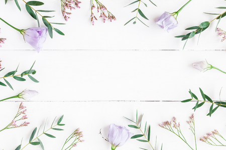 Flowers composition. Frame made of various flowers and eucalyptus branches on white background. Flat lay, top view