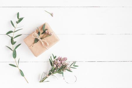 꽃 조성입니다. 흰색 나무 배경에 선물, 핑크 꽃과 유칼립투스 분기. 평평한 평면, 평면도