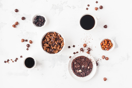 Cups of coffee, chocolate cake, chocolate muesli on white background. Flat lay, top view, copy space