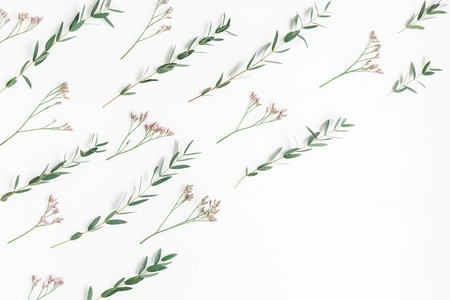 Flowers composition. Pattern made of pink flowers and eucalyptus branches on white background. Flat lay, top view 写真素材