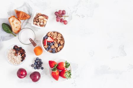 Healthy breakfast with muesli, yogurt, fruits, berries, nuts on white background. Flat lay, top view