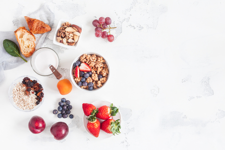 Healthy breakfast with muesli, yogurt, fruits, berries, nuts on white background. Flat lay, top view