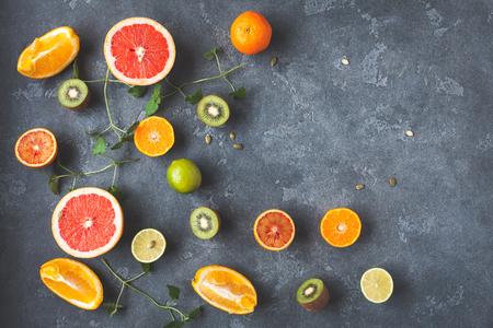 Colorful fresh fruit on dark background. Orange, tangerine, lime, kiwi, grapefruit. Fruit background. Summer food concept. Flat lay, top view, copy space