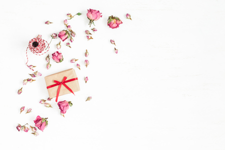 Flowers composition. Gift and dried rose flowers on white background. Flat lay, top view Archivio Fotografico