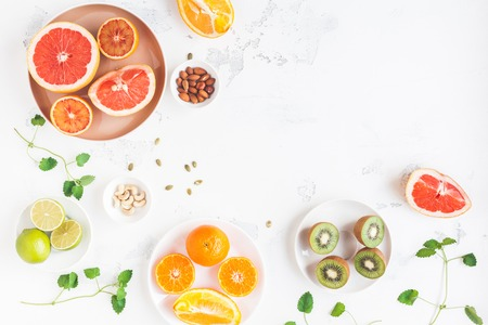 Colorful fresh fruit on white table. Orange, tangerine, lime, kiwi, grapefruit. Summer fruit. Flat lay, top view, copy space