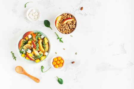 ミューズリー、桃のサラダ、新鮮な桃、白い背景の上で朝食します。健康食品のコンセプトです。フラット横たわっていた、トップ ビュー