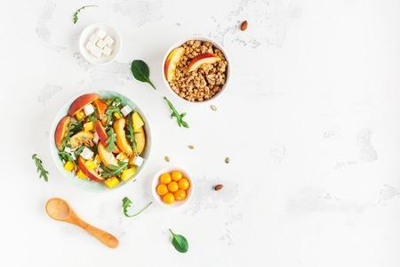 Ontbijt met muesli, perziksalade, verse perziken, op witte achtergrond. Gezond voedselconcept. Plat leggen, bovenaanzicht