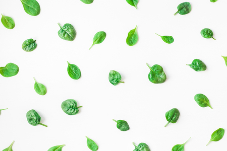 Spinach leaves on white background. Pattern made of spinach. Flat lay, top view