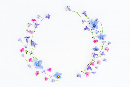 Wreath made of bell flowers, pansy flowers and pink flowers on white background. Flat lay, top view Stock Photo