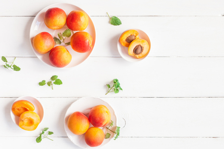 Abrikoos op houten witte achtergrond. Gesneden abrikozen bovenaanzicht, plat lag, kopie ruimte Stockfoto