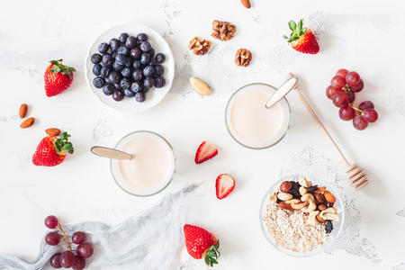 Breakfast with muesli, yogurt, strawberry, blueberry, nuts on white background. Healthy food concept. Flat lay, top view