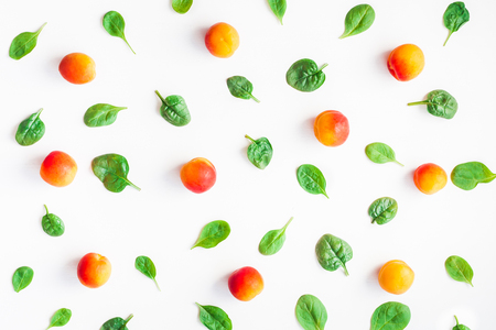 Apricot and spinach leaves on white background. Fruit pattern. Top view, flat lay
