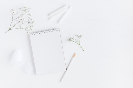 Workspace with notebook, paper blank, gypsophila flowers, pencils. Wedding concept. Flat lay, top view