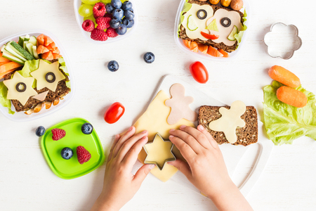 School lunch box for kids. Cooking. Child's hands. Backto school. Top view, flat lay Archivio Fotografico