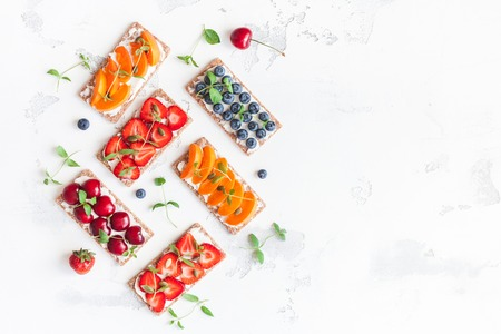 Snack with crispbread, cream cheese and fresh fruits on white background. Healthy food concept. Flat lay, top view, copy space Stock fotó
