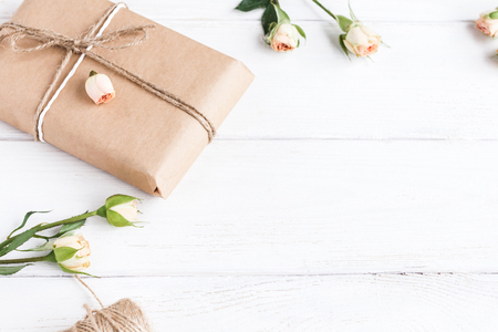 Gift and roses on wooden white background. Top view, flat lay Stock Photo