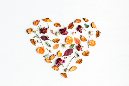 Heart symbol made of dried flowers and autumn leaves. Top view, flat lay