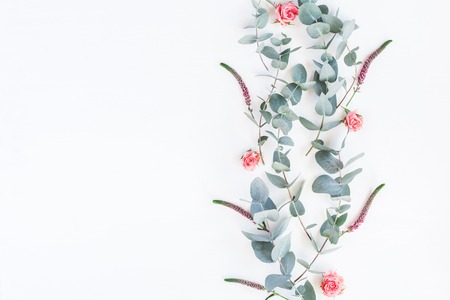 Flowers composition. Pattern made of rose flowers and eucalyptus branches on white background. Flat lay, top view, copy space Stock Photo