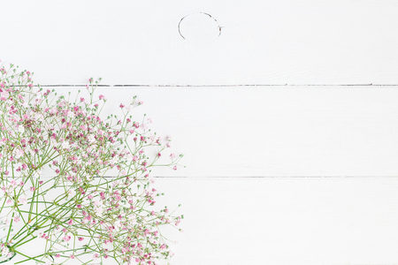 Flowers composition. Floral frame made of pink gypsophila flowers on white wooden background. Flat lay, top view, copy space