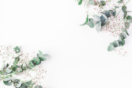 Flowers composition. Frame made of of pink gypsophila flowers and eucalyptus branches on white background. Flat lay, top view, copy space