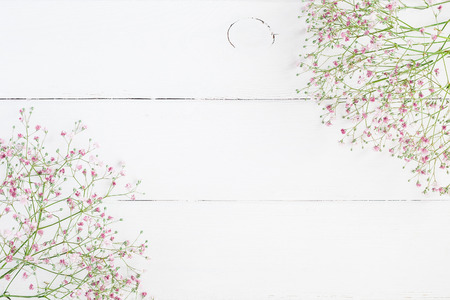 Floral frame made of pink gypsophila flowers on white wooden background. Flat lay, top view, copy space