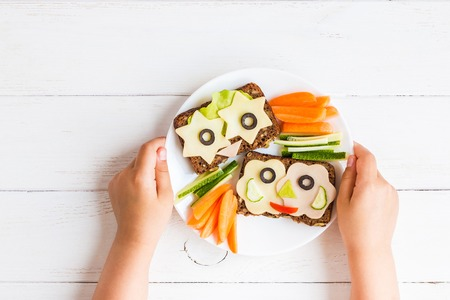 School lunch box for kids. Child's hands. Top view, flat lay Archivio Fotografico
