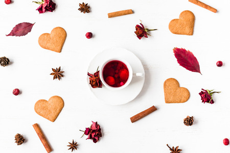 cup of fruit tea with autumn leaves, cookie, cinnamon sticks, star anise, cones, dry roses, top view, flat lay