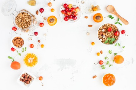 Breakfast with muesli, fruits, berries, nuts on white background. Healthy food concept. Flat lay, top view, copy space Stock Photo - 83355131