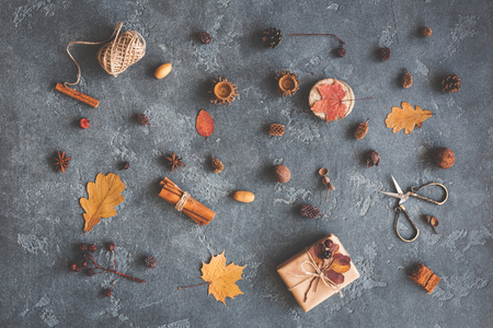 Autumn composition. Gift, autumn leaves, cinnamon sticks, anise stars, pine cones on black background. Flat lay, top view