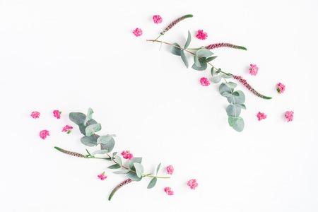 Blumenzusammensetzung. Das Feld, das von den rosa Blumen und von den Eukalyptuszweigen gemacht wird, verzweigt sich auf weißem Hintergrund. Flache Lage, Draufsicht, Textfreiraum Standard-Bild - 83355156