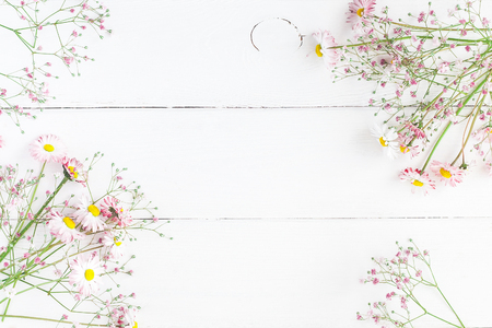 Flowers composition. Floral frame made of pink gypsophila flowers and daisy flowers on white wooden background. Flat lay, top view, copy space Banco de Imagens