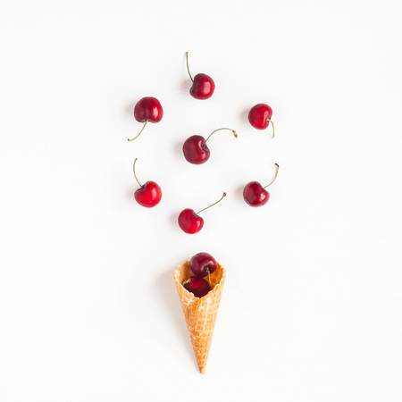 Cherry in waffle cone on white background. Creative food concept. Flat lay, top view, square