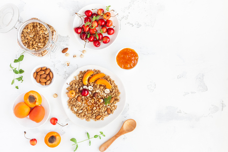 Breakfast with muesli, fruits, berries, nuts on white background. Healthy food concept. Flat lay, top view, copy space