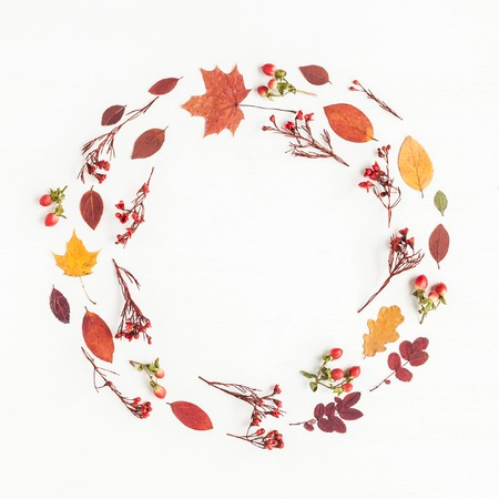 Autumn composition. Wreath made of autumn flowers and leaves on white background. Flat lay, top view, copy space