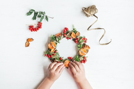 Autumn. Child making handmade autumn wreath. Top view, flat lay Фото со стока