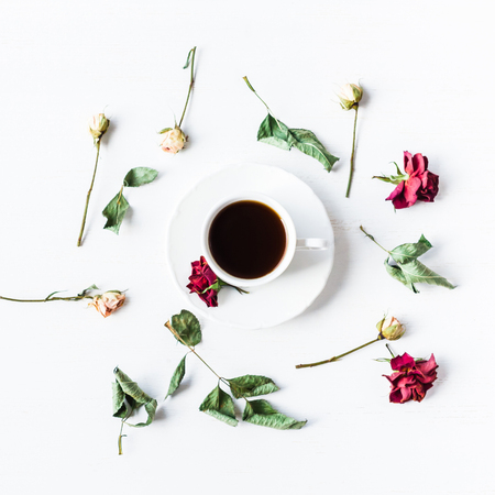 cup of coffee with dried rose flowers, square, top view, flat lay