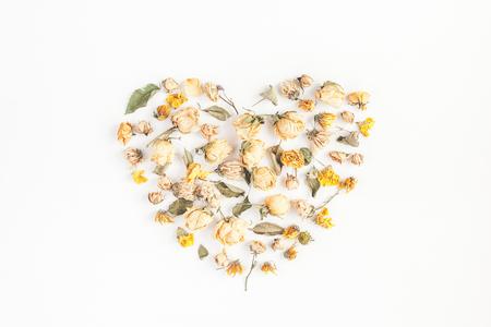 Herbstzusammensetzung. Herz-Symbol aus getrockneten Herbst Blumen und Blätter auf weißem Hintergrund. Draufsicht, flach liegen Standard-Bild - 84912123