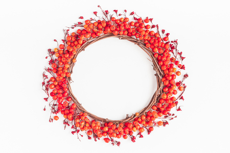 Autumn composition. Wreath made of rowan berries and autumn red flowers. Flat lay, top view, copy space