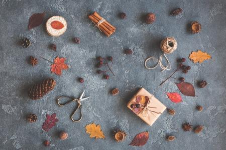 Осенняя композиция. Подарок, осенние листья, палочки корицы, анисовые звезды, сосновые шишки на черном фоне. Плоский, вид сверху Фото со стока