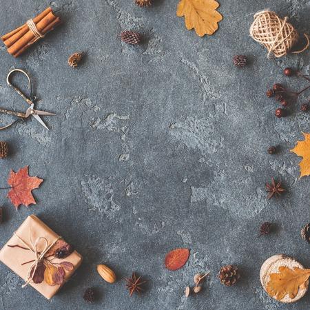 Composición del otoño. Regalo, hojas de otoño, palitos de canela, anís estrellas, pino conos sobre fondo negro. Flat lay, vista desde arriba, copia espacio