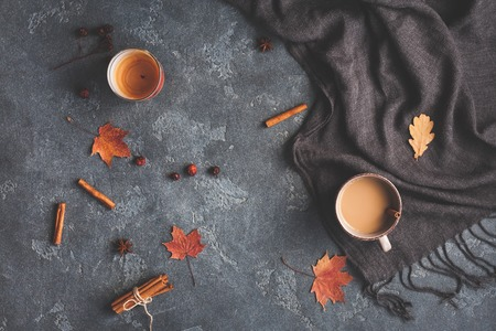 Autumn composition. Cup of coffee, blanket, autumn leaves, cinnamon sticks on black background. Flat lay, top view
