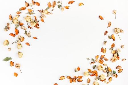 Jesienna kompozycja. Rama wykonana z jesieni suszonych kwiatów i liści na białym tle. Płaski, górny widok, miejsce na kopię