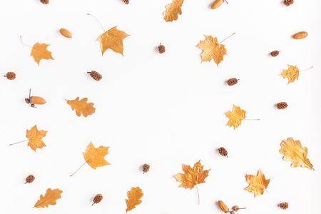 Composición del otoño. Marco hecho de las hojas del árbol de arce del otoño y de los conos del pino en el fondo blanco. Vista plana