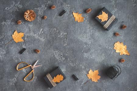 Jesienna kompozycja. Prezenty, jesienne liści złote, szyszki sosnowe, akcesoria na czarnym tle. Płaski, górny widok