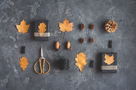 Autumn composition. Gifts, autumn golden leaves, pine cones, accessories on black background. Flat lay, top view Archivio Fotografico