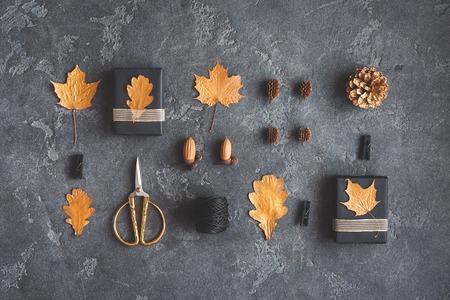 Composición del otoño. Regalos, hojas de oro de otoño, conos de pino, accesorios sobre fondo negro. Vista plana