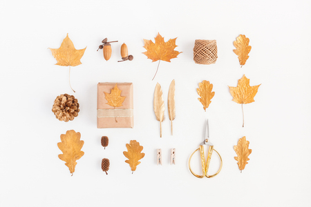 Осенняя композиция. Подарок, осенние золотые листья, сосновые шишки, аксессуары на белом фоне. Плоский, вид сверху