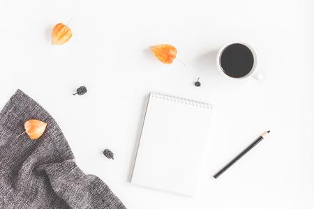 Espacio de trabajo de otoño. Taza de café, bufanda, bloc de notas, flores de otoño sobre fondo blanco. Vista plana Foto de archivo